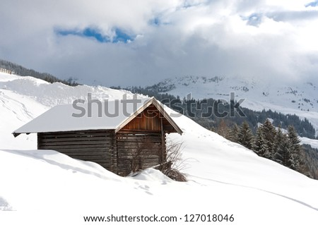 winter scene in mountains with wooden house