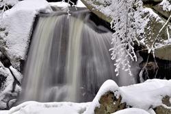 Winter scene in Willard Brook State Park, Massachusetts. Small waterfall (Trap Falls) framed by fresh fallen snow.