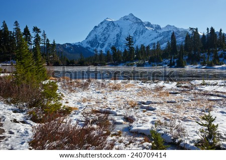 Winter scene of Mount Shuksan and Picture lake frozen over with ice on a clear day.