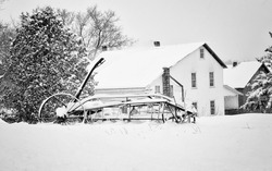 Winter scene with a horse drawn hay rake and a Amish farmhouse