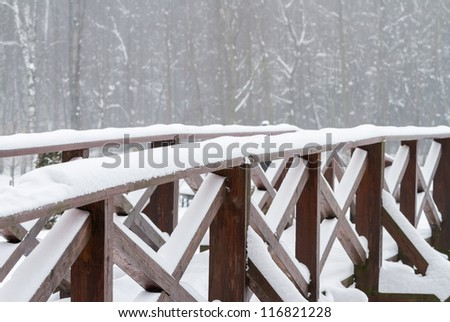 Winter scene with bridge in the forest - stock photo