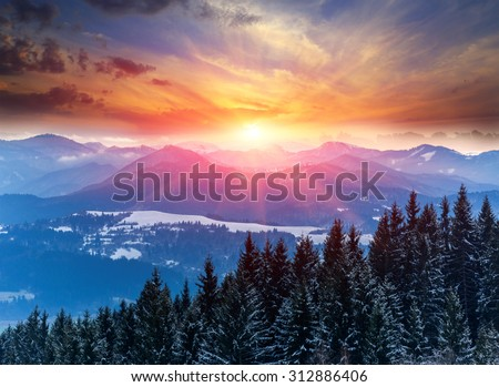 Winter scene with sunset in mountains #312886406