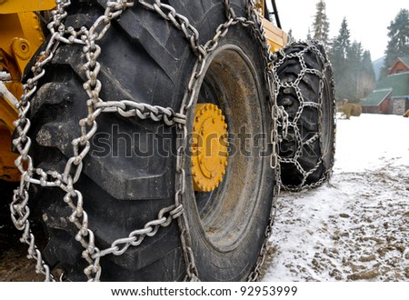 Winter scenery. Logging machine giant wheels equipped with snow chains