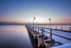 Winter scenery. Old pier in Gdynia Orlowo Poland with ice formations icicles. Frozen Sea Baltic seasonal specific.