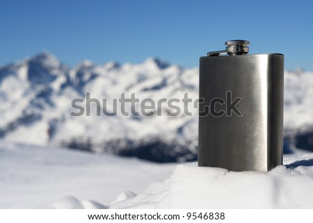 winter season on snowy mountain and silver flask