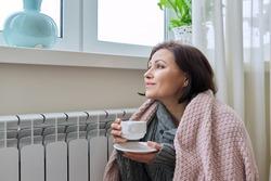 Winter season, woman warming up near home heating radiator