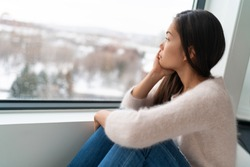 Winter seasonal affective disorder SAD depression mood alone Asian girl feeling lonely - stress, anxiety, melancholy emotions. Sadness at home.