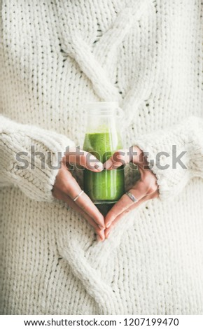 Winter seasonal smoothie drink detox. Female in warm sweater holding bottle of green smoothie or juice making heart shape with her hands. Clean eating, weight loss, healthy dieting food concept