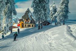 Winter ski resort with wooden lodges near ski piste. Snow covered pine trees and sporty skiers on the ski slope, Poiana Brasov ski resort, Transylvania, Romania, Europe