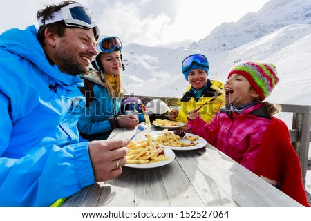 Winter ski skiers enjoying lunch in winter mountains