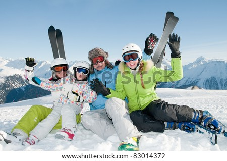 Winter, ski, sun and fun - happy family in ski resort - stock photo