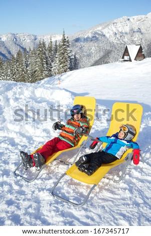 Winter, ski, sun and fun - kids in winter resort resting in the deck chair