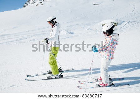 Winter skiing - girl skiing with mother in ski resort