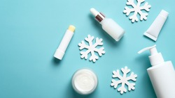 Winter skin care beauty products and snowflakes on pastel blue background. Pump bottle, serum, jar or cream, lipstick, tube packaging design. Flat lay, top view.