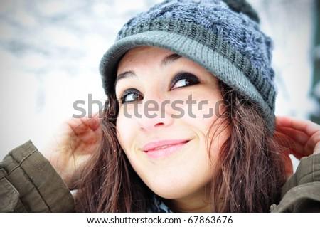 Winter smile. Happy girl in winter set-up, smiling looking upwards