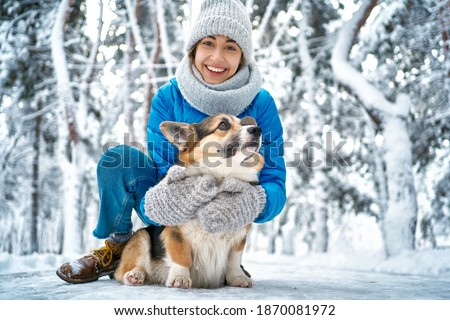 Winter smiling woman in warm hat and scarf hugging with her pet Welsh Corgi dog, having fun in snow at winter park