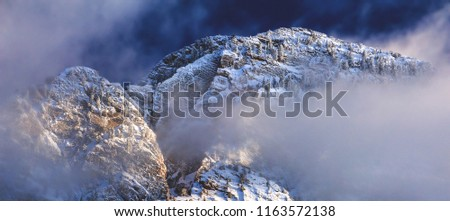 Winter snow clings to the granite face and peaks of Mount Timpanogos in the Wasatch Front mountains just above Salt Lake City, Utah, USA.