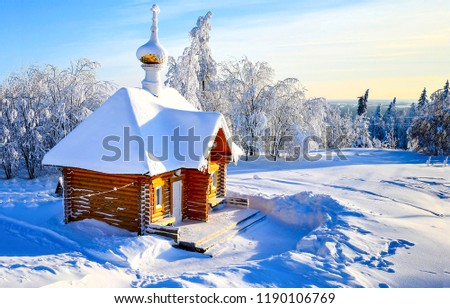 Winter snow covered wooden church view. Wooden church in winter snow forest scene. Winter church in snowy forest. Winter snow forest church view