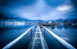 Winter snow lake pier view. Lake houses in winter mountain snow scene. Mountain lake house in winter snow landscape. Winter lake snowy pier view