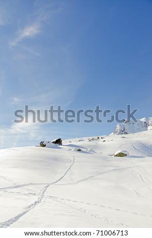 Winter snow mountain landscape with ski traces under blue sky. Sunshine. Rock. Alps. France.