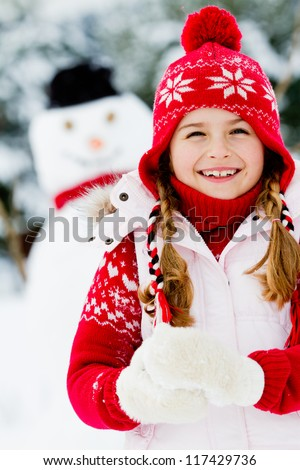 Winter, snowman - lovely girl has a fun in snow