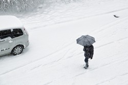 Winter snowy city scene with pedestrian and car.
