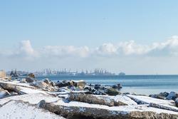 Winter snowy landscape by the sea. Sea port in the winter.