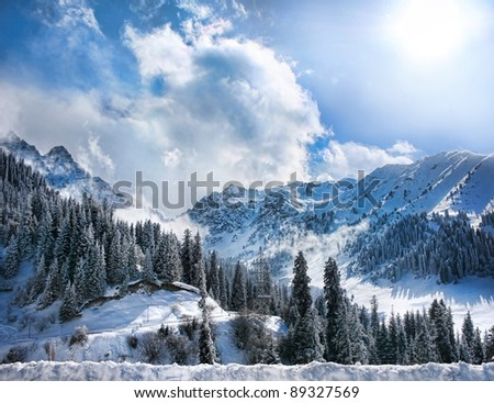 Winter Snowy Mountains valley with fog and sun in Chumbulak, Almaty, Kazakhstan