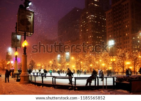 Winter snowy night in a city. Background with silhouettes of people enjoying ice skating during beautiful snowy winter night in downtown of Chicago in shallow depth of field.