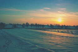 Winter snowy scenery. Arable field covered with snow at sunset