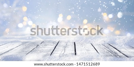 Winter snowy stage background with wooden flooring and Christmas lights on blue background, banner format, copy space.