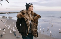 winter,spring portrait of trendy girl,wearing warm casual fur coat ,and cool knitted hat, Sea background,warm toned colors.lifestyle image,dreaming girl.walking alone,enjoy her time,sea-gull around