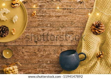Winter styled scene on a rustic wooden background with cozy blanket and faery lights. Ceramic tray and mug with nuts and biscuits. Central copy space.