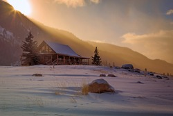 Winter sunrise at a log cabin in the Utah mountains, USA.
