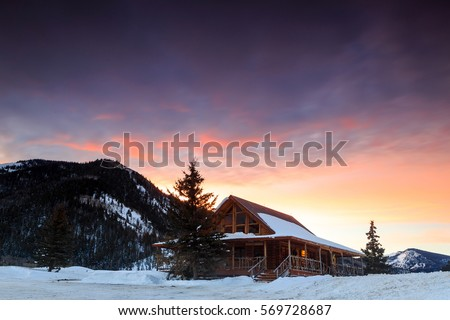 winter sunrise with a log cabin ...