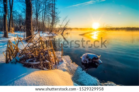 Winter sunset forest river landscape. Sunset winter forest river view. Winter forest river sunset fog scene. Winter river sunset landscape