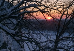Winter sunset over the frozen river Ufa on the background of the cliff