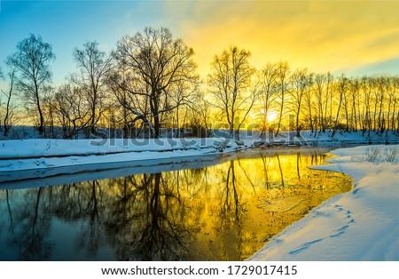 Winter sunset rural river landscape. Sunset river in winter scene