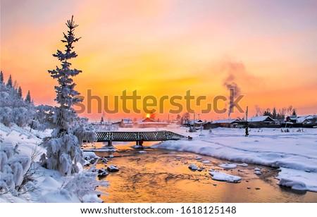 Winter sunset rural river landscape. Sunset winter rural river view. Winter village river sunset scene. Winter sunset river