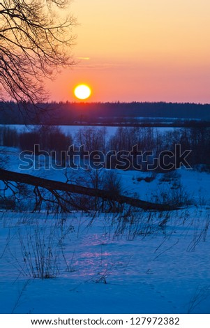 Winter sunset. Winter rural landscape with the river at sunset.