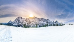 Winter sunshine over snowy mountains - Snowy panorama with the Austrian Alps, the green coniferous forests and a valley covered by white snow.