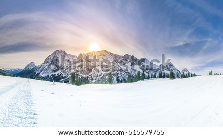 Winter sunshine over snowy mountains - Snowy panorama with the Austrian Alps, the green coniferous forests and a valley covered by white snow. #515579755