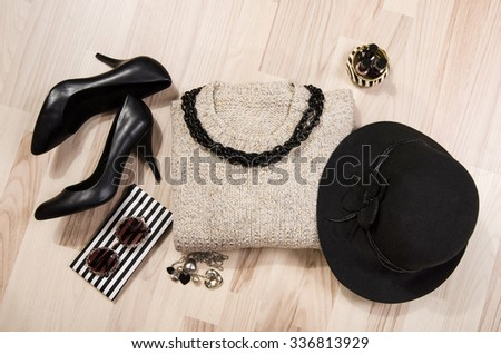 Shutterstock Winter sweater and accessories arranged on the floor. Woman sweater with silver accessories, high heels, black hat, necklace and nail polish.