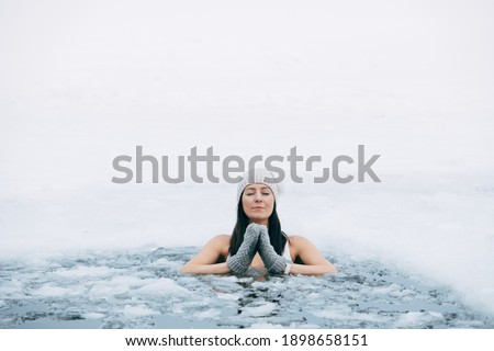 Winter swimming. Woman in frozen lake ice hole. Swimmers wellness in icy water. How to swim in cold water. Beautiful young female in zen meditation. Gray hat and gloves swimming clothes. Nature lake