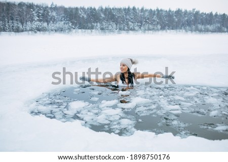Winter swimming. Woman in frozen lake ice hole. Swimmers wellness in icy water. How to swim in cold water. Beautiful young female smiling. Gray hat and gloves swimming clothes. Nature lake in forest