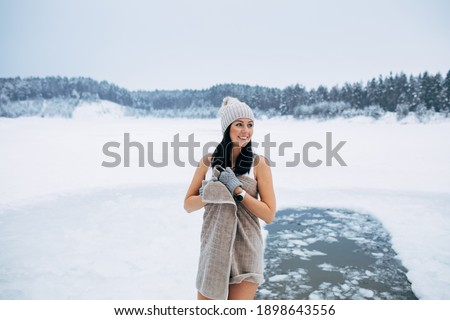 Winter swimming. Woman ready to swim in ice water. How to swim in cold water. Beautiful young woman wrapped in a towel and swimming clothes. Gray hat and gloves. People and nature lake in the forest.