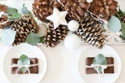Winter table centerpiece with brown pinecones, white ornaments, plates, brown napkins, eucalyptus leaves, white tablecloth and rustic vintage straw wreath.
