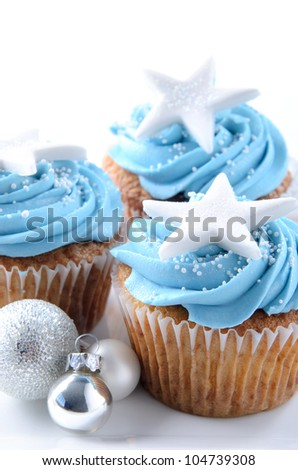 Winter theme christmas cupcakes with blue frosting and silver christmas ornaments