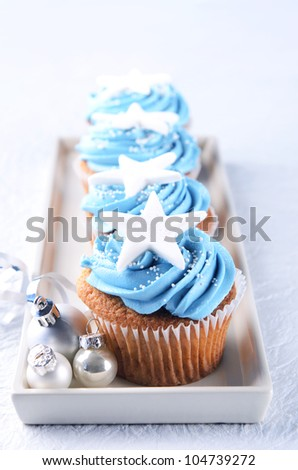 Winter theme christmas cupcakes with blue icing and silver xmas baubles