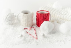 Winter themed stilllife with two mugs of tea, heart shaped sugar canes, knitted decor in white and red colors, horizontal orientation